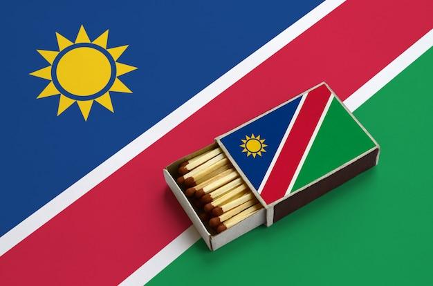 ナミビアの旗は開いているマッチ箱に表示され、マッチで満たされ、大きな旗の上にあります