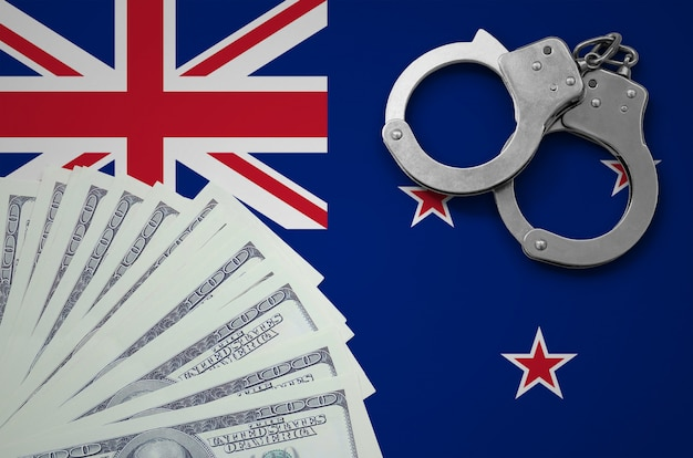 手錠とドルの束を持つニュージーランドの旗。米国通貨での違法な銀行業務の概念