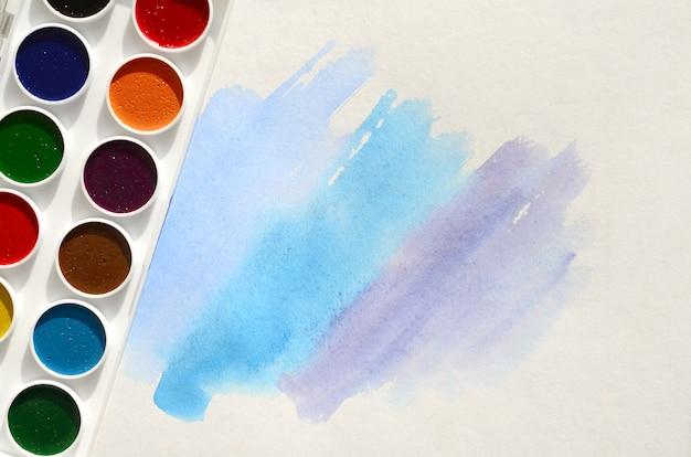 Новый набор акварели лежит на листе бумаги, на котором изображен абстрактный акварельный рисунок в виде синих штрихов
