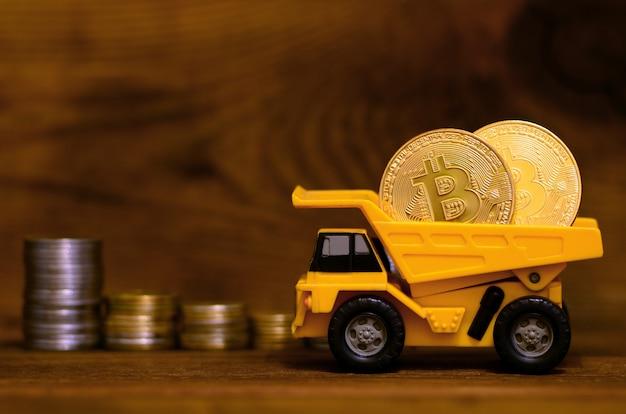 黄色いおもちゃのダンパーに光沢のあるゴールデンビットコインが入っています