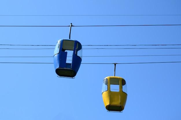 晴天の青と黄色の旅客ケーブルウェイキャビン
