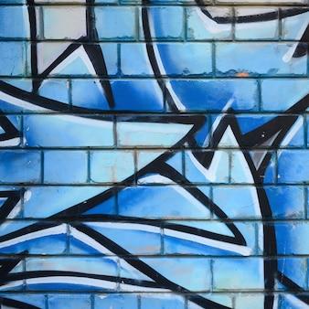 落書き図面の断片。ペイントで飾られた古い壁は、ストリートアート文化のスタイルで汚れています。色付きの背景テクスチャ