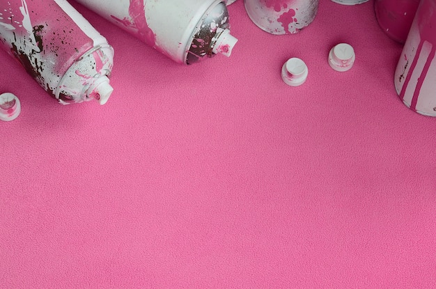 いくつかの中古のピンクのエアロゾルスプレー缶とペンキが滴るノズル