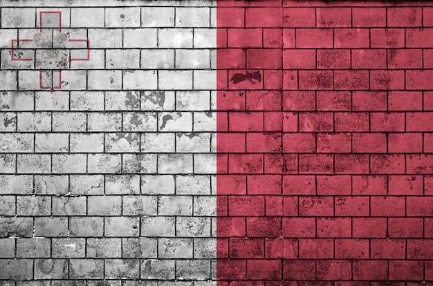 マルタの旗は古いレンガの壁に描かれています