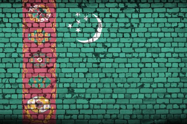 古いレンガの壁にトルクメニスタンの国旗が描かれています