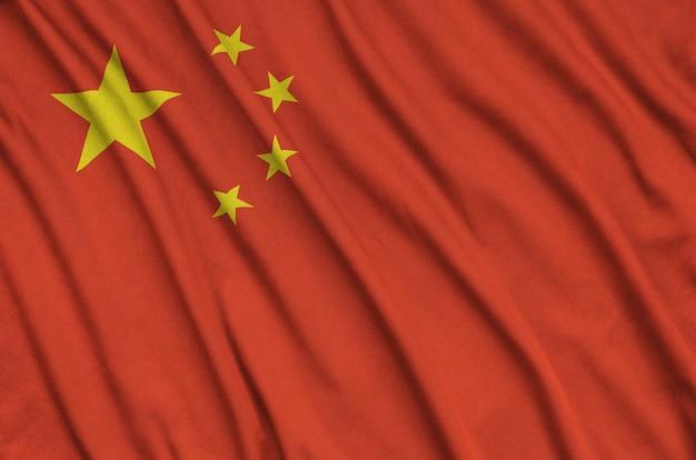 Флаг китая изображен на спортивной ткани с множеством складок.