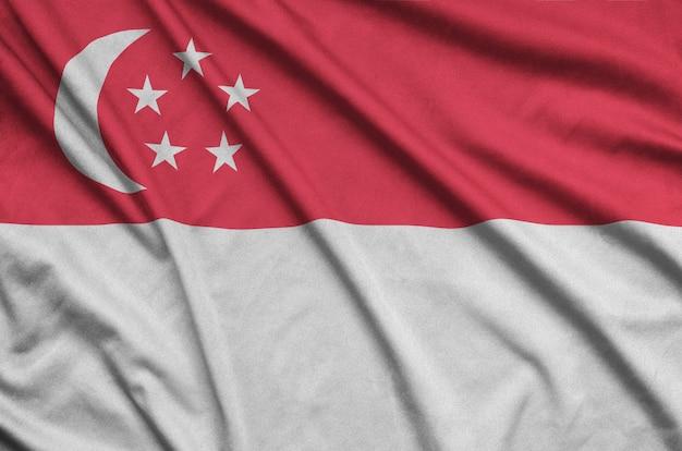 Флаг сингапура изображен на спортивной ткани с множеством складок.