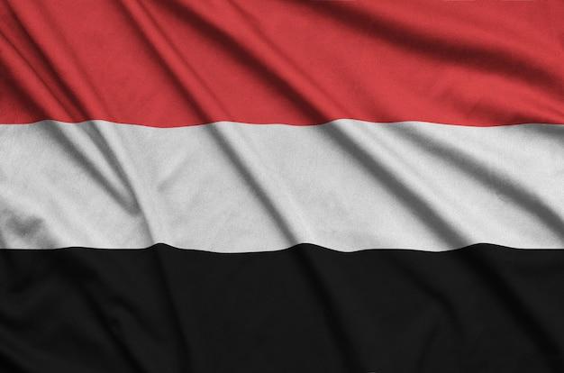 Йеменский флаг изображен на спортивной ткани с множеством складок.