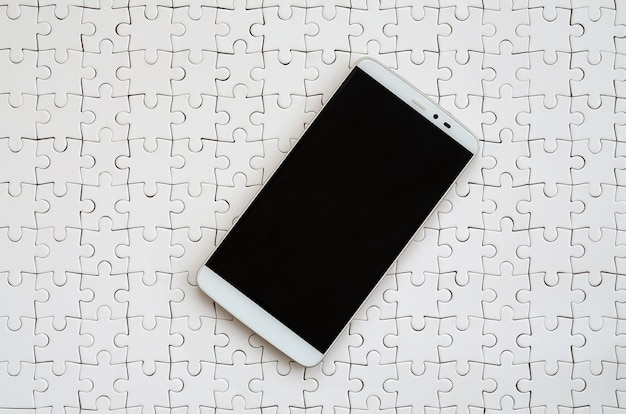 タッチスクリーンを備えた現代の大きなスマートフォンは、組み立てられた状態で白いジグソーパズルの上にあります