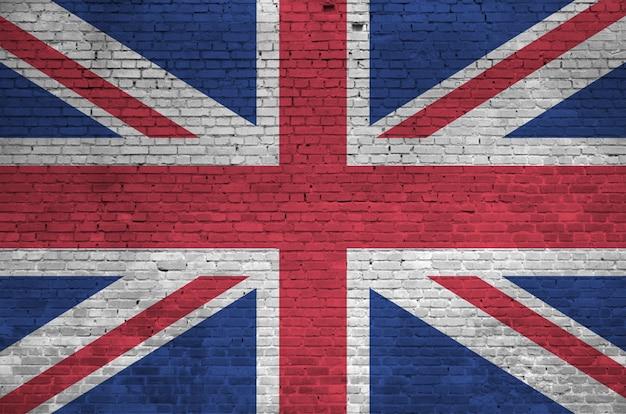古いレンガの壁にペンキの色で描かれた英国の旗。大きなレンガ壁石積みの背景にテクスチャバナー