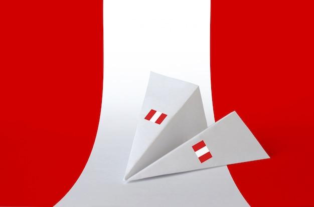 紙の折り紙飛行機に描かれたペルーの国旗。手作りのアートコンセプト