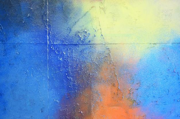 Большой фрагмент рисунка граффити нанесен на стену аэрозольной краской. градиент между несколькими цветами осуществляется путем распыления краски. абстрактное фоновое изображение