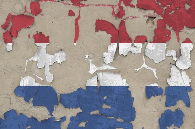 古い時代遅れの乱雑なコンクリート壁のクローズアップにペンキの色で描かれたオランダの国旗。大まかな背景にテクスチャバナー