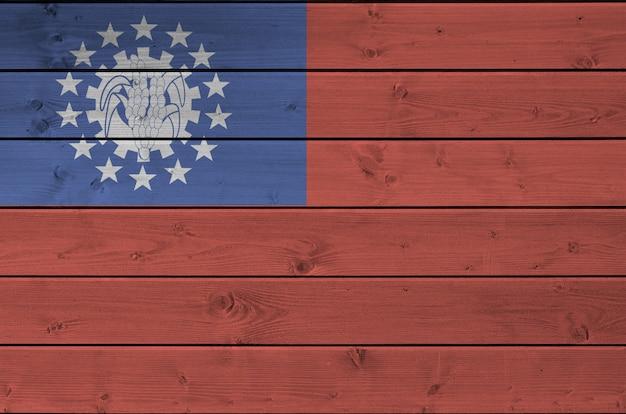 Флаг мьянмы изображен в яркие краски цвета на старые деревянные стены.