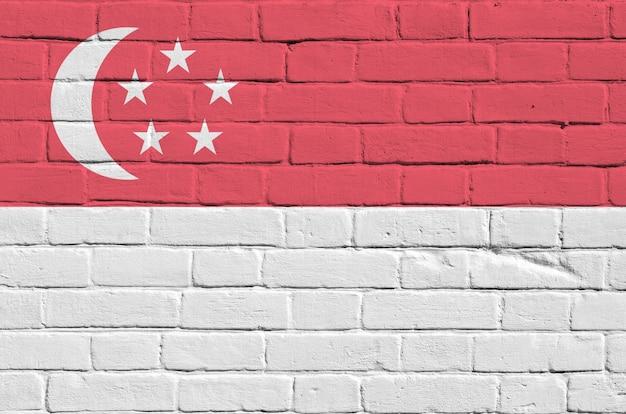 古いレンガの壁にペンキの色で描かれたシンガポールの国旗。大きなレンガ壁石積みの背景にテクスチャバナー