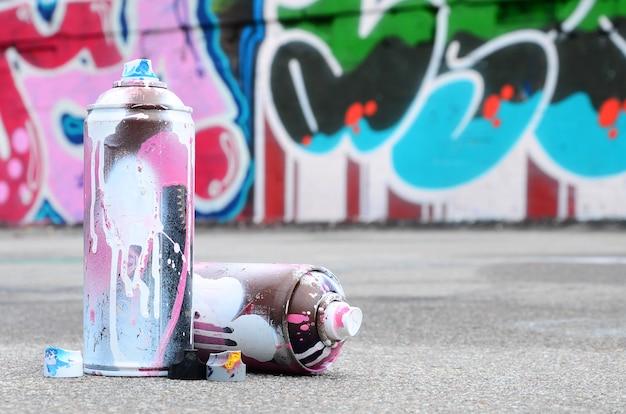 Несколько использованных аэрозольных баллончиков с розовой и белой краской и колпачки для распыления краски под давлением лежат на асфальте возле окрашенной стены в цветных рисунках граффити.