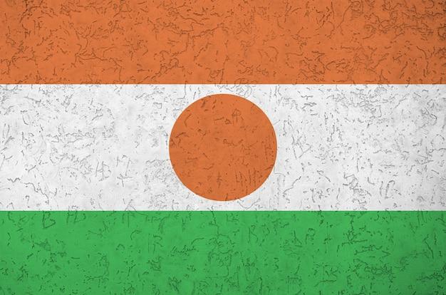 古い救済左官壁に明るいペンキ色で描かれたニジェールの国旗。大まかな背景に織り目加工のバナー