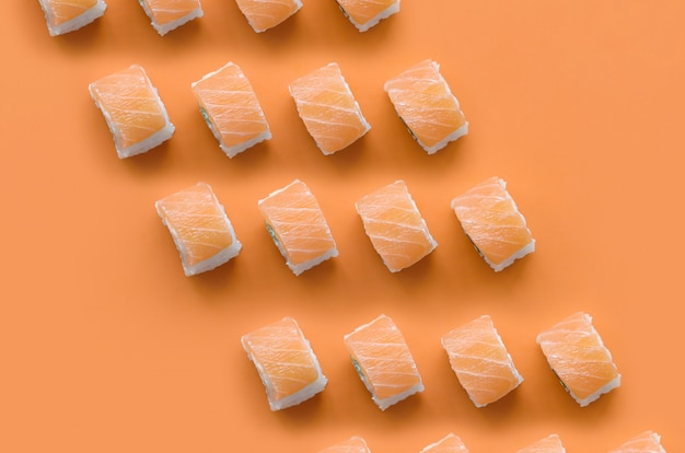 Филадельфия роллы с лососем на оранжевом фоне. минимализм, вид сверху, плоская планировка с японской едой
