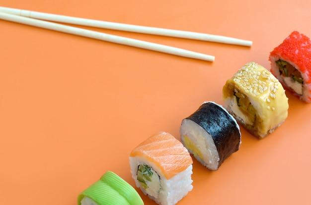 さまざまな種類のアジアの寿司はオレンジ色の背景にロールバックします。ミニマリズムトップビューフラット横たわっていた日本食
