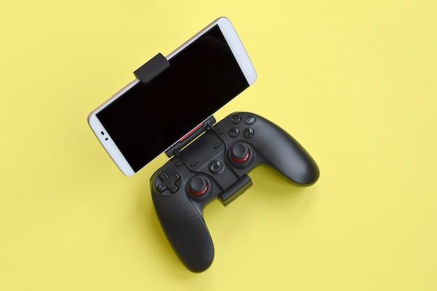 黄色の背景にスマートフォンのモダンな黒のゲームパッド。モバイルビデオゲームデバイス