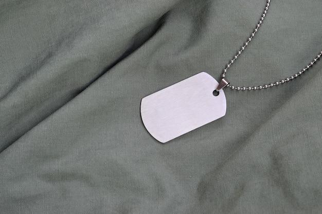 ダークグリーンの疲労ユニフォームに犬のタグが付いた銀色のミリタリービーズ