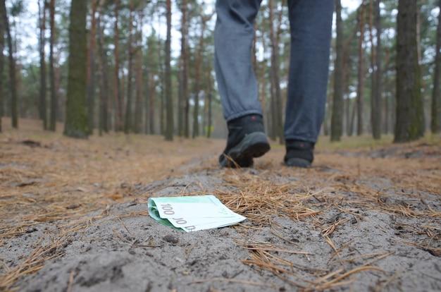 若い男は、ロシアの秋のモミの木の道で彼のユーロ紙幣を失います。不注意とお金を失う概念