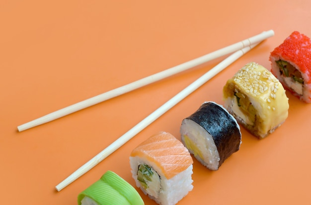 Разные виды азиатских кренов суш на оранжевой предпосылке. минимализм с плоской планировкой с японской едой