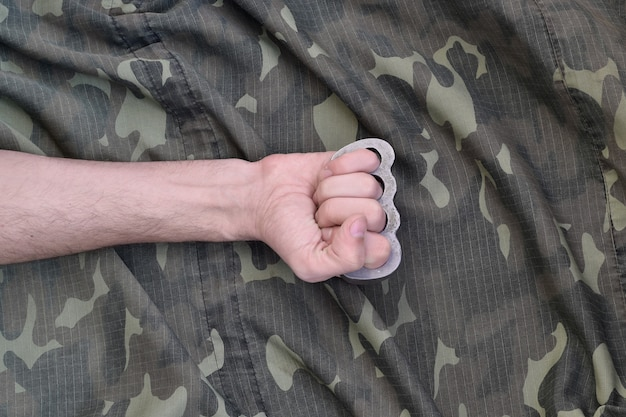 Мужской кулак с латунными костяшками на фоне камуфляжной куртки. концепция культуры скинхедов, оружие ближнего боя ручной работы