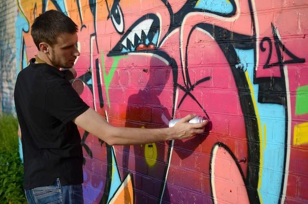バックパックと彼の首に防毒マスクを持つ若いグラフィティアーティストは、レンガの壁にピンクの色調でカラフルなグラフィティをペイントします。ストリートアートと現代の絵画プロセス