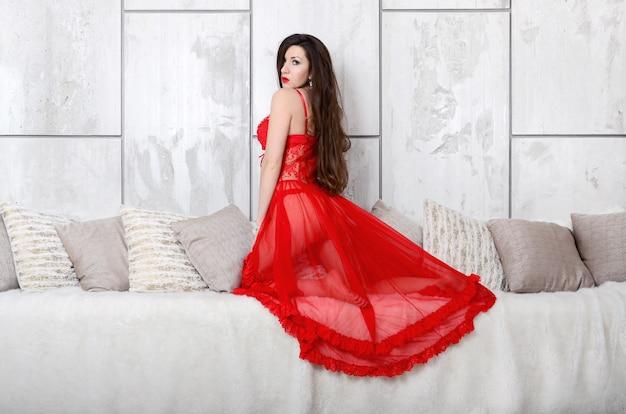 赤いペニョワールランジェリーの透明なドレスと多くの枕とクリーミーなベッドの横にあるランジェリーのセクシーな若い女性