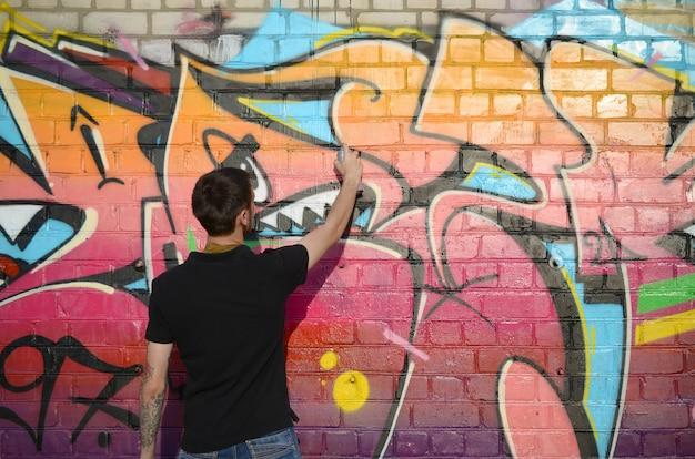 バックパックと彼の首に防毒マスクを持つ若いグラフィティアーティストは、レンガの壁にピンクの色調でカラフルなグラフィティを描く