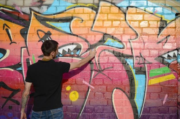 彼の首にバックパックと防毒マスクを持つ若いグラフィティアーティストは、カラフルな落書きを描く