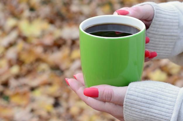 Женщина в белом свитере держит чашку зеленого кофе