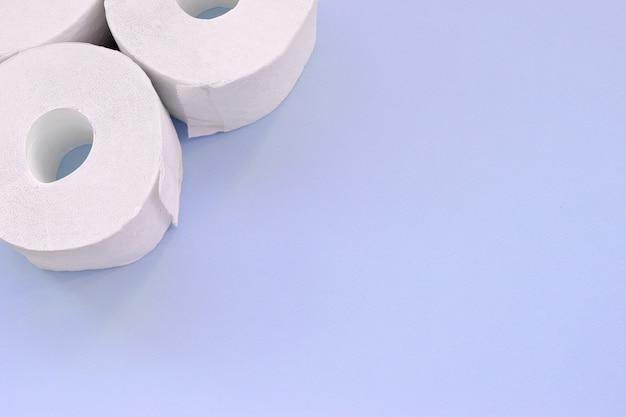 Коронавирус пандемии паники покупки концепции. несколько новых рулонов туалетной бумаги на светло-синем фоне. минималистичная плоская композиция с копией пространства