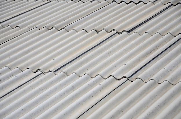 アスベスト材料で作られた古いサンプルの灰色のスレート屋根の断片