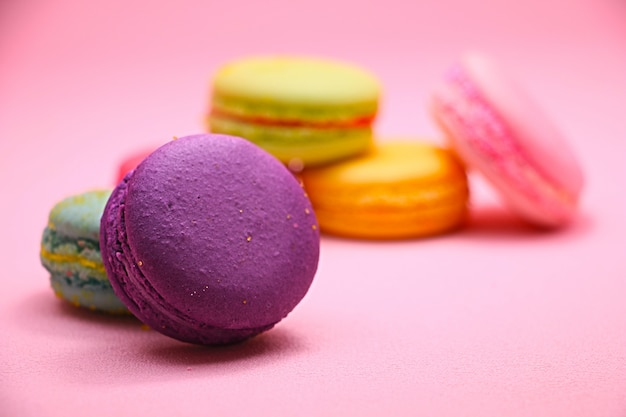 カラフルなケーキマカロンまたは正面からのピンクの背景のマカロン、クッキー