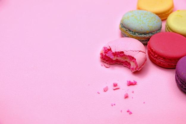 カラフルなケーキのマカロンやマカロン、トップビュー、カラフルなクッキーからピンクの背景に
