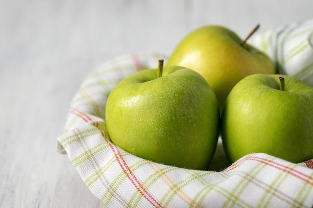 木製のテーブルの上の水の滴の緑のりんご