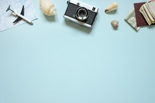Предметы для летнего отдыха: фотоаппарат, паспорт, деньги. синий фон, вид сверху. копировать пространство