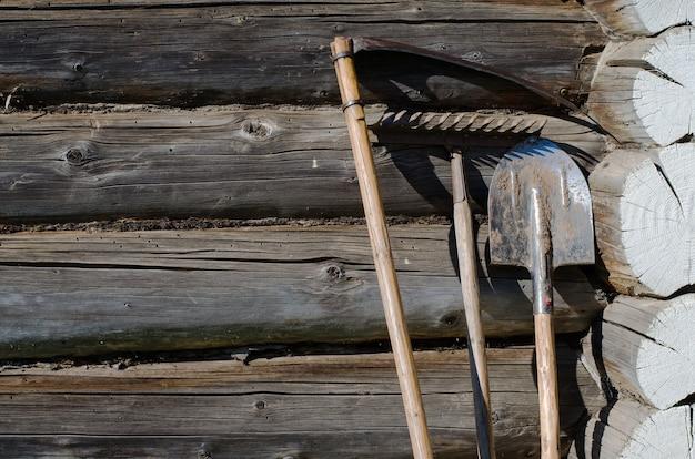 ガーデンツール - 鎌、シャベル、熊手。木の丸太から作られた農村住居の壁