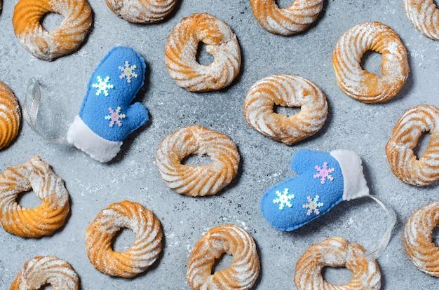 Рождественские печенья узор на сером фоне. две синие зимние перчатки.