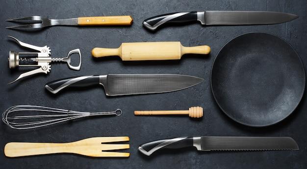 木製および金属製の台所用品と黒い皿。料理用のツール。暗い背景。平置き