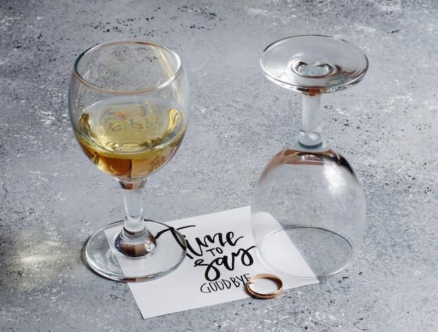 お別れの時間だ。ホワイトペーパーシートの碑文。ガラスグラスに白ワイン。金の婚約指輪。