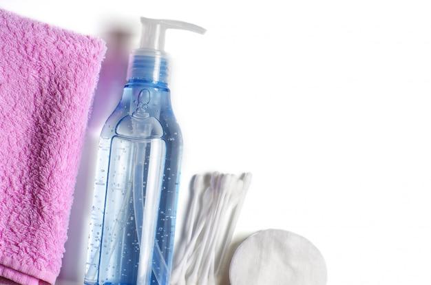 Женские аксессуары для снятия макияжа. гель в прозрачной бутылке, ватные палочки, ватные диски, розовое полотенце.