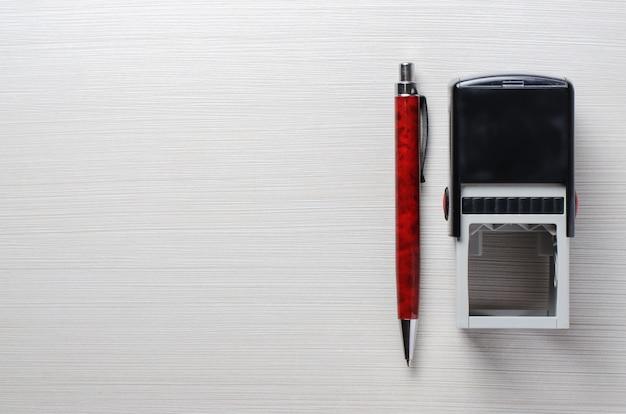 Штамп и перьевая ручка на столе