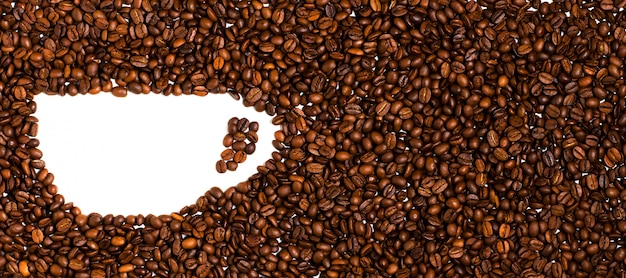 Фон из жареных кофейных зерен. пространство для текста в форме кофейной чашки