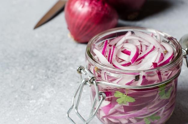 ガラスの瓶に酢で赤玉ねぎのみじん切り。肉や魚料理のおいしいおかず。ライトグレー
