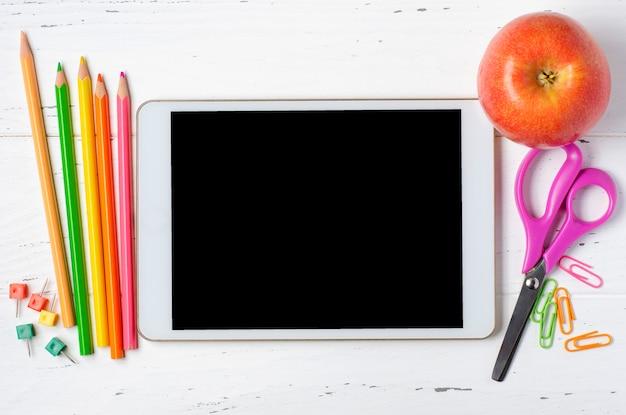 の木製の背景に空の画面とオフィス用品のタブレット。学童や子供のためのオンライン学習のためのコンセプトアプリ。コピースペース