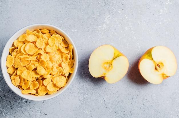青いカップとアップルスライスのコーンフレーク。朝の便利な朝食。コピースペース