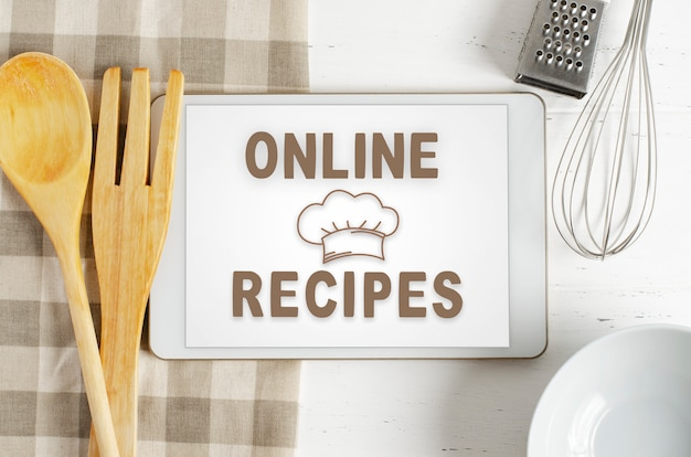 Интернет рецепты. поваренная книга в планшетном компьютере. кухонные принадлежности.